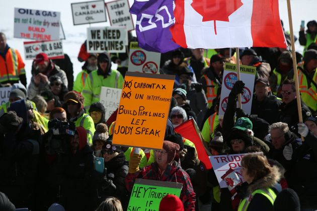 Supporters hold signs during a United We Roll Convoy in front of Parliament Hill in Ottawa on Feb. 19,