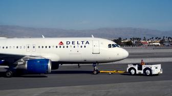 PALM SPRINGS, CALIFORNIA - FEBRUARY 25, 2019:  A Delta Air Llnes ground crew member pushes a passenger aircraft from the gate at Palm Springs International Airport in Palm Springs, California. (Photo by Robert Alexander/Getty Images)