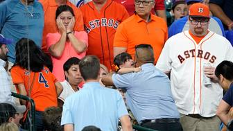 A young child is carried from the stands after being injured by a foul ball off the bat of Chicago Cubs' Albert Almora Jr. during the fourth inning of a baseball game against the Houston Astros Wednesday, May 29, 2019, in Houston. (AP Photo/David J. Phillip)