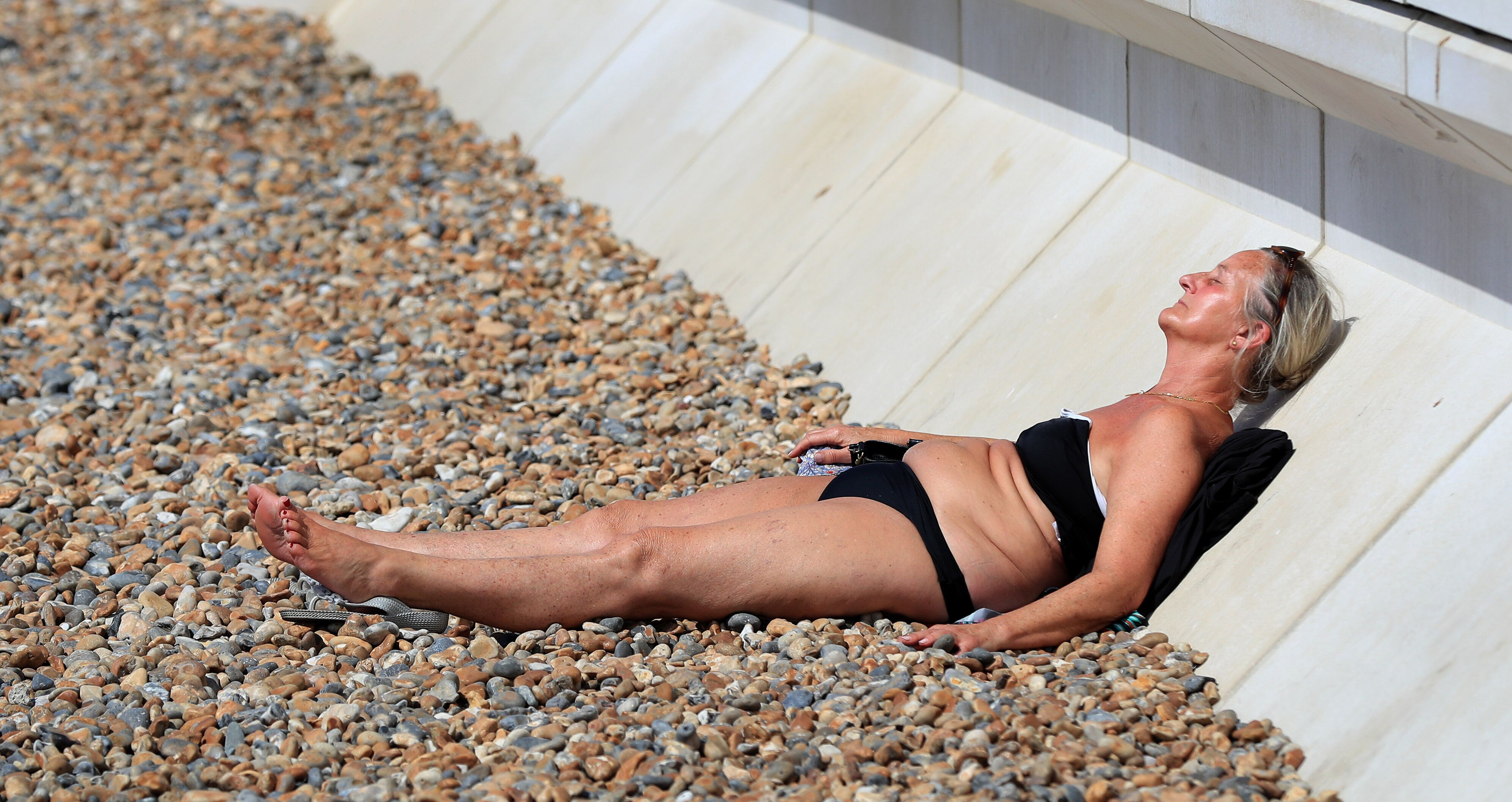 A woman relaxes on Brighton beach (Photo by Gareth Fuller/PA Images via Getty Images)