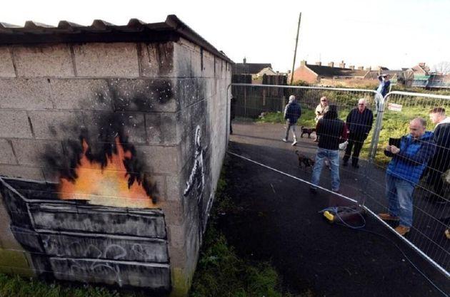Pessoas olham obra do muralista Banksy no País de