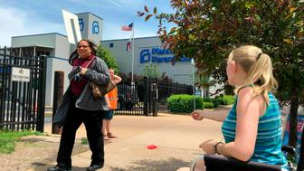 FILE - In this May 17, 2019 file photo, Teresa Pettis, right, greets a passerby outside the Planned Parenthood clinic in St. Louis. Pettis was one of a small number of abortion opponents protesting outside the clinic on the day the Missouri Legislature passed a sweeping measure banning abortions at eight weeks of pregnancy. Planned Parenthood says Missouri's only abortion clinic could be closed by the end of the week because the state is threatening to not renew its license, which expires Friday, May 31. (AP Photo/Jim Salter, File)