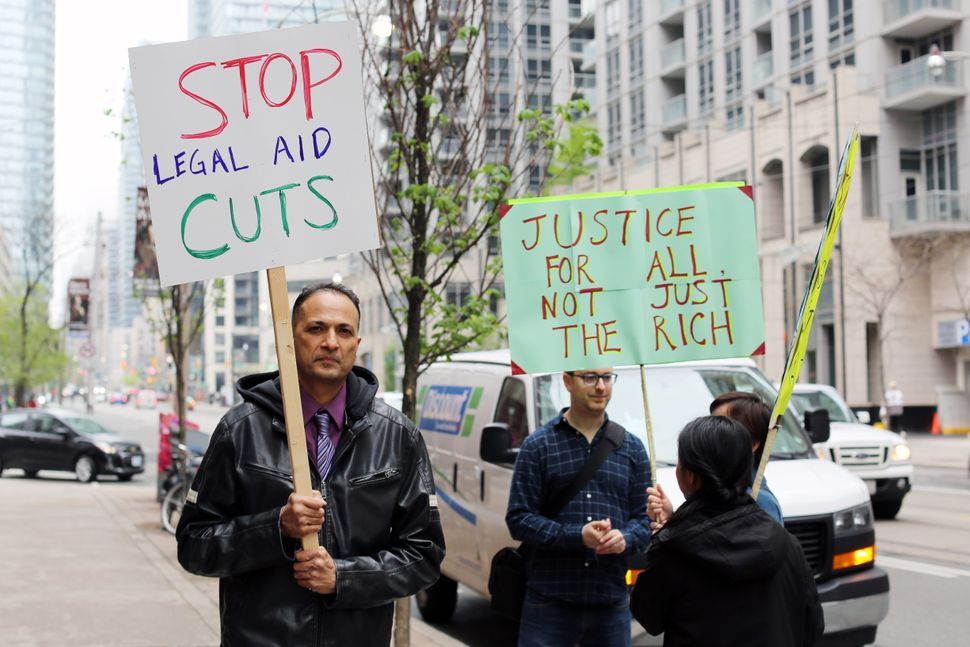 Protesters outside the Ministry of Attorney General's office in Toronto took a stand against the cuts...