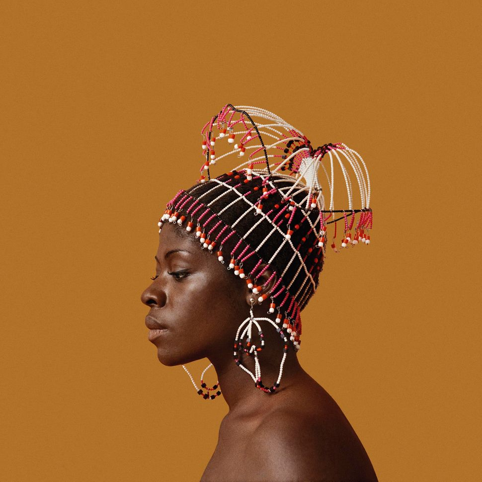 "Sikolo Brathwaite wearing a headpiece designed by Carolee Prince, African Jazz-Art Society & Studios (AJASS), Harlem, circa 1968. From ""Kwame Brathwaite: Black Is Beautiful"" (Aperture, 2019)."