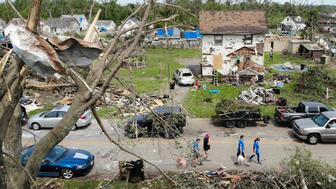 Residents walk through a tornado damaged neighborhood, Wednesday, May 29, 2019, in Dayton, Ohio, as clean up efforts begin. Tens of thousands of Ohio residents were still without power or water in the aftermath of strong tornadoes that spun through the Midwest earlier in the week. (AP Photo/John Minchillo)