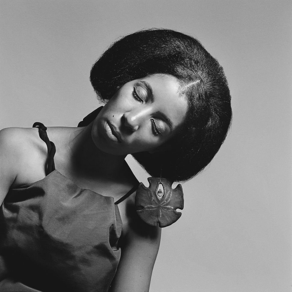 "Carolee Prince, African Jazz-Art Society & Studios (AJASS), Harlem, circa 1964, wearing her own jewelry designs. Prince created much of the jewelry and headpieces featured in Brathwaite's work. From ""Kwame Brathwaite: Black Is Beautiful"" (Aperture, 2019)."