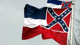 Two Mississippi state flags wave outside the Capitol in Jackson, Miss., in this Jan. 22, 2019 photograph. Mississippi legislative committees are again killing bills to either remove the Confederate battle emblem from the state flag or require universities to fly the state banner. The state has used the flag since 1894 and it is the last state banner featuring the Confederate emblem that critics say is racist and supporters say is a symbol of history. (AP Photo/Rogelio V. Solis)