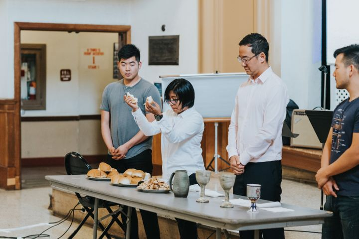 Pastor Eula Pagdilao of the First Progressive Church in Los Angeles blesses bread during a service at the PAAC conference.