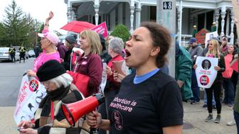 In this Thursday, May 23, 2019 photo, Tammy Brown, 36, of Cranston, R.I, leads the crowd in chants outside a fundraiser for the Rhode Island Senate Democrats political action committee in Providence, R.I. Protesters gathered at the fundraiser to pressure legislative leaders to bring a bill seeking to protect abortion rights to the Senate floor for a vote. (AP Photo/Jennifer McDermott)
