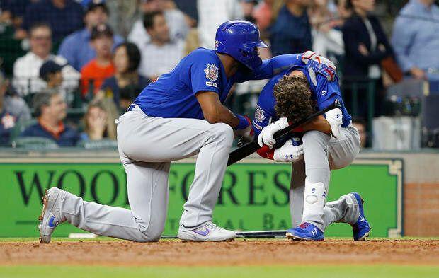 打球が少女に直撃した後に打席で膝をついて号泣するカブスのアルバート・アルモラJr.選手(写真右)と同選手を慰めるチームメイトのジェイソン・ヘイワード選手(写真左)