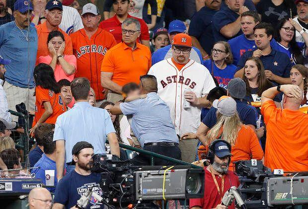 打球が直撃した少女を抱きかかえる家族と見られる男性と、事態に驚く観客たち。