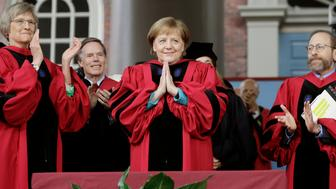 German Chancellor Angela Merkel, center, places her hands together as she receives applause while being presented with an honorary Doctor of Laws degree as former Harvard President Drew Faust, left, and Harvard Provost Alan Garber, right, look on during Harvard University commencement exercises, Thursday, May 30, 2019, on the schools campus, in Cambridge, Mass. (AP Photo/Steven Senne)