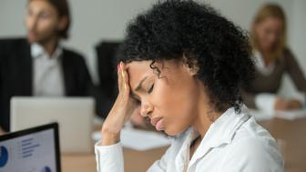 African american businesswoman feeling unwell suffering from headache migraine touching forehead at team meeting, upset black woman employee frustrated by business problem or work stress, head shot