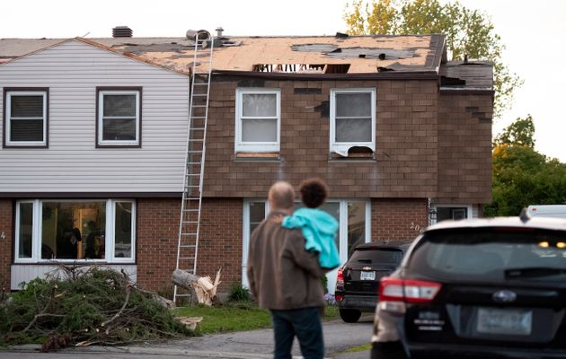 People look at the home's roof which was damaged by a tornado in the Ottawa suburb of Orleans on June...