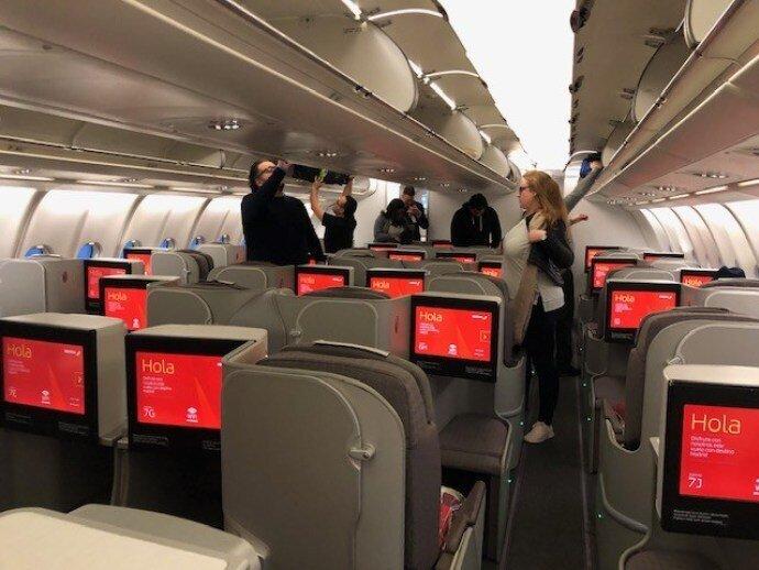 一進入機艙,映入眼簾的是好多個寫著 Hola 大紅色的螢幕,紅色是伊比利航空主題色,從螢幕、過夜包、菜單封面、毯子,都是大紅色的設計