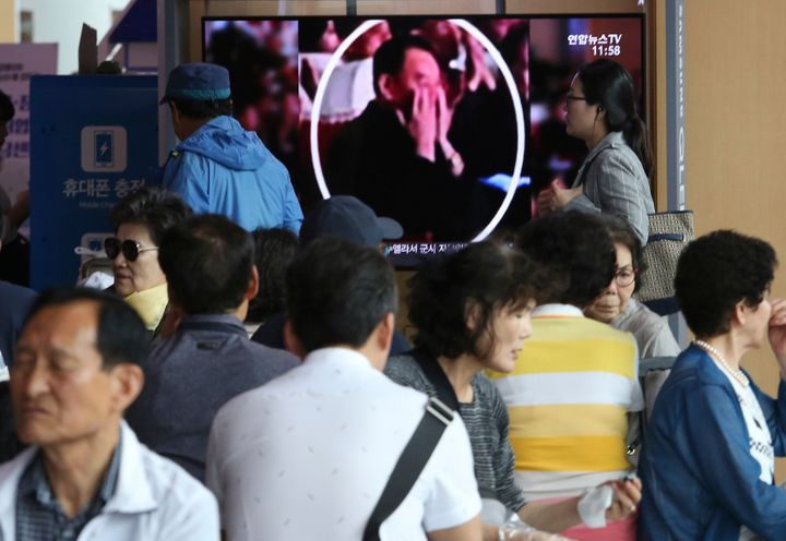 People watch a TV screen showing an image of senior North Korean official Kim Yong Chol in a musical performance by the wives