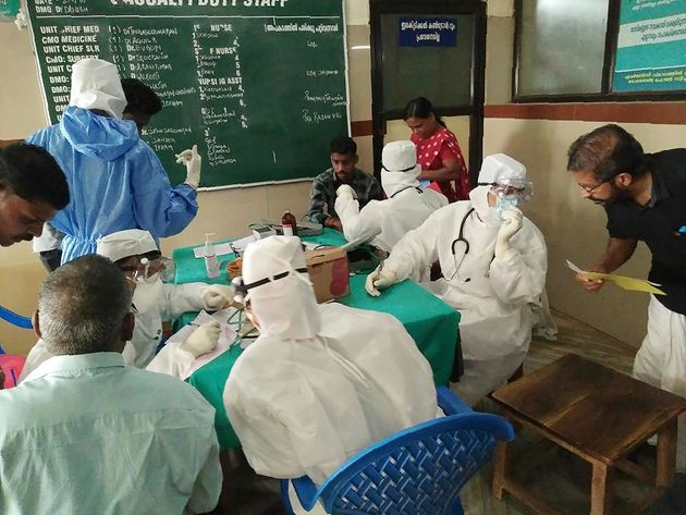 Medical personnel wearing protective suits check patients at the Medical College hospital in Kozhikode...