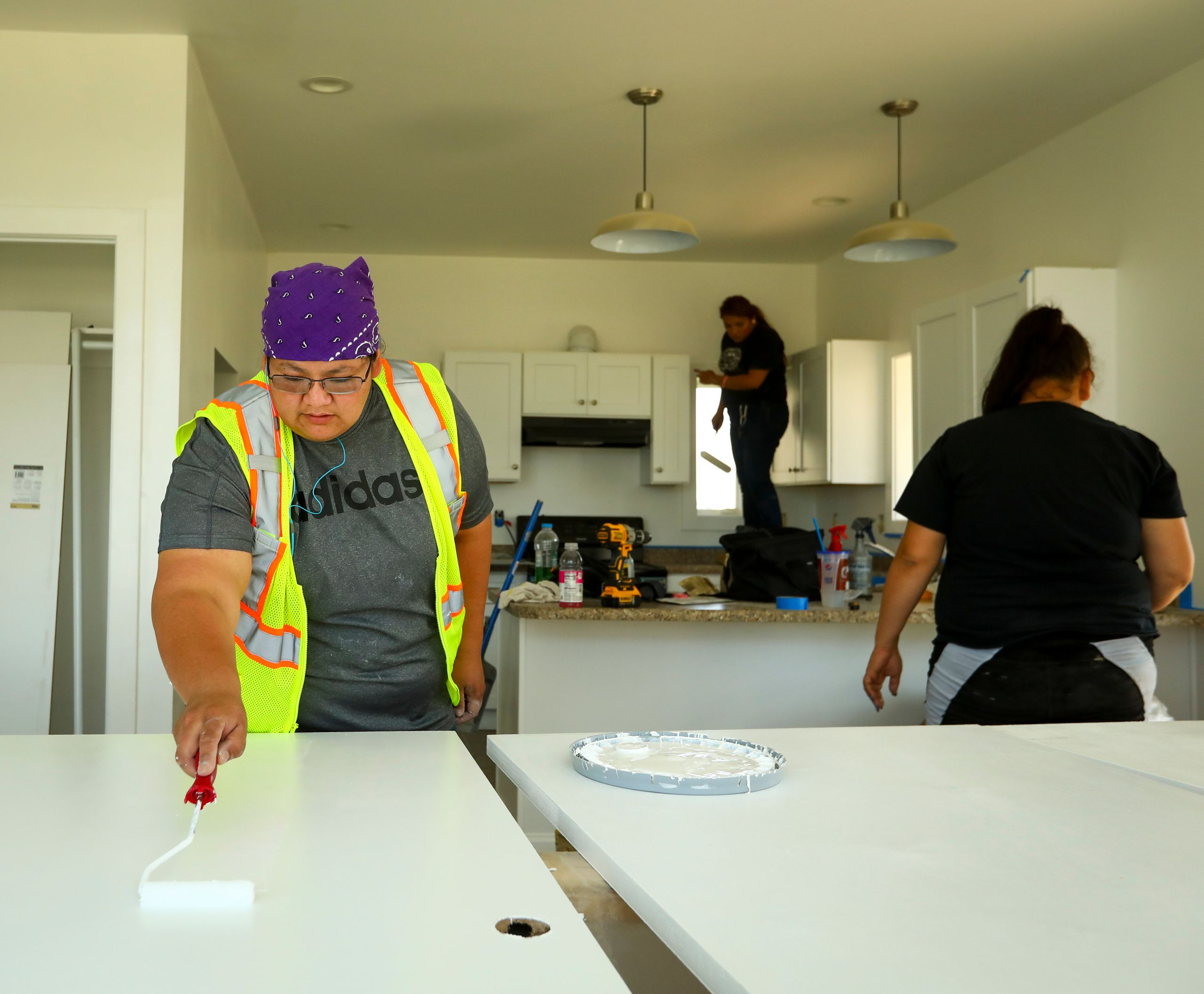 Marie Kills Warrior, 26, applies a second coat of paint to doors in a Thunder Valley CDC affordable housing unit on the Pine