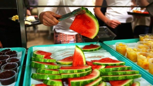 A high school student selects a slice of watermelon for lunch in this file photo. More students are using apps to have restau