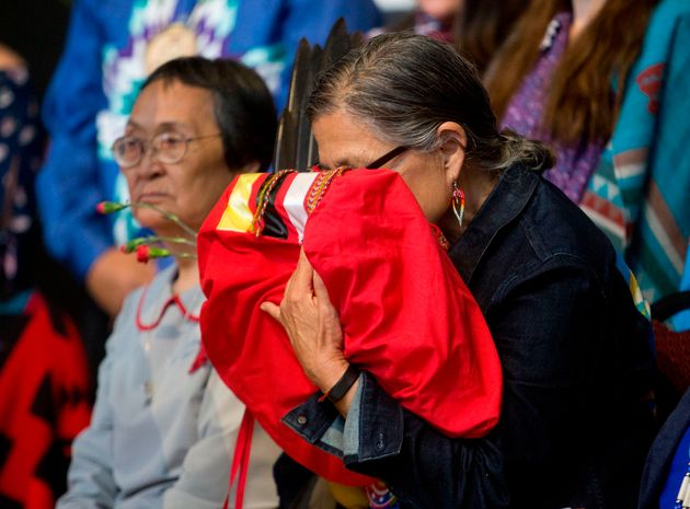A woman embraces the final copy of the report at a public closing ceremony in Gatineau, Quebec on June...