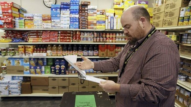 A high school principal looks over a supply list while standing in the school's community food pantry in New London, Iowa. Fo