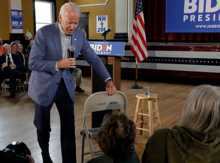 Former vice president and Democratic presidential candidate Joe Biden brings a chair over for a woman in the audience during