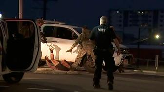 In this image made from video, police proceed to apprehend a suspect on the ground next to a white truck, Tuesday, June 4, 2019, in Darwin Australia. Media reports say a gunman has killed at least four people in the Australian city of Darwin. Northern Territory Police Duty Superintendent Lee Morgan says a 45-year-old man was in custody following Tuesday's shooting. (Australian Broadcasting Corporation via AP)