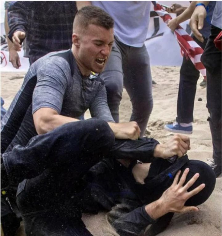Robert Rundo, a founder of the neo-Nazi Rise Above Movement, punches a counter-protester during a political rally at Bolsa Ch
