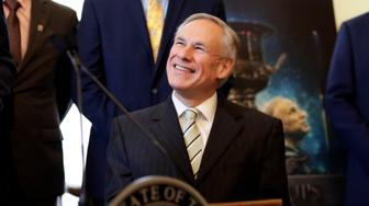A poster with an image of Texas Gov. Greg Abbott is seen behind Abbott at a news conference where he was presented the Governor's Cup by Site Selection Magazine, Monday, March 4, 2019, in Austin, Texas. Texas won for having the most qualified projects of any state according to their data. (AP Photo/Eric Gay)