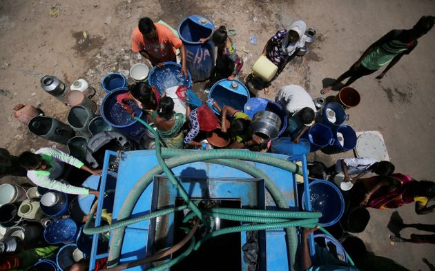 People fill their empty containers with water from municipal corporation tanker in