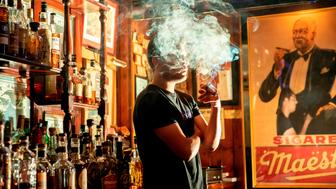Marc Dominguez, bartender at Buena Vista Cigar Club, smokes a cigar in the lounge in Beverly Hills, California, on May 21, 2019. - Posh Beverly Hills is poised to outlaw the sale of all tobacco products -- except at cigar lounges where the rich and famous like Arnold Schwarzenegger are assured they can keep puffing away. Under the proposed ordinance, described as the first of its kind in the nation, the sale of tobacco products would be banned starting in January 2021. An initial vote on the measure is scheduled for late Tuesday, with a final vote is set for June 4. (Photo by Kyle Grillot / AFP)        (Photo credit should read KYLE GRILLOT/AFP/Getty Images)