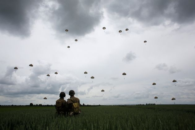 WWII enthusiasts watch French and British parachutists jumping during a commemorative parachute jump...