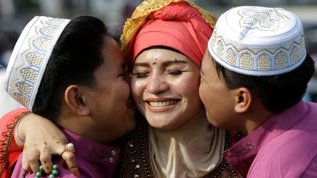 Filipino Muslim boys kiss their mother as they pose for pictures after Eid al-Fitr prayers to mark the end of the holy fasting month of Ramadan in Manila, Philippines on Wednesday, June 5, 2019. (AP Photo/Aaron Favila)