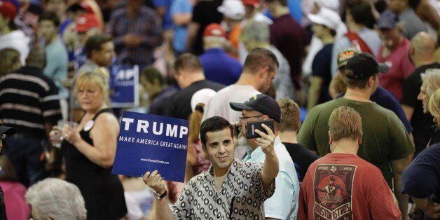 A supporter of Republican presidential candidate Donald Trump takes a picture while holding a sign before the start of a rall