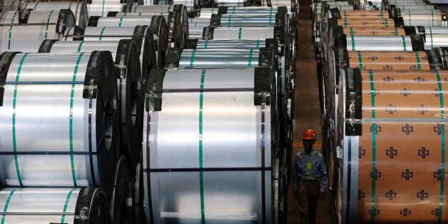 A worker walks past rolls of steel inside the China Steel Corporation factory, in Kaohsiung, southern Taiwan August 26, 2016.