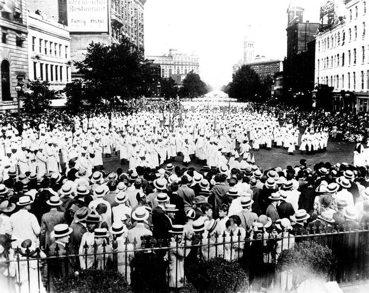 Members of the Ku Klux Klan, wearing traditional white robes, parade down Pennsylvania Avenue past the Treasury Building in W