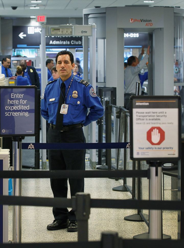 MIAMI, FL - OCTOBER 04:  A TSA agent waits for passengers to use the TSA PreCheck lane being implemented by the Transportatio