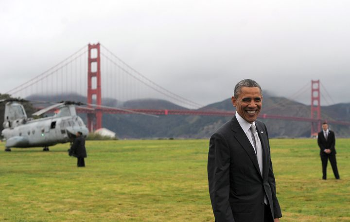 US President Barack Obama smiles before boarding Marine One helicopter from a field overlooking the iconic golden gate bridge