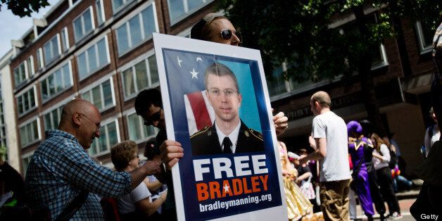 LONDON, UNITED KINGDOM - JUNE 29: A man participating in the LGBT parade carries a placard about imprisoned US military whist
