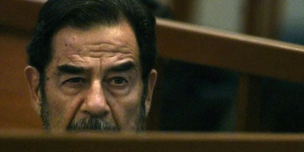 Baghdad, IRAQ:  Former Iraqi leader Saddam Hussein listens to prosecutors during his trial held in Baghdad's heavily-fortifie