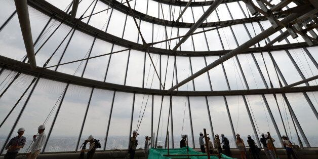 This photograph taken on August 2, 2013 shows journalists inside the under-construction Shanghai Tower in Shanghai. Work on t