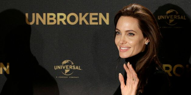 "U.S. director Angelina Jolie waves as she leaves after a photo call for the movie ""Unbroken'"" in Berlin, Thursday, Nov. 27, 2"