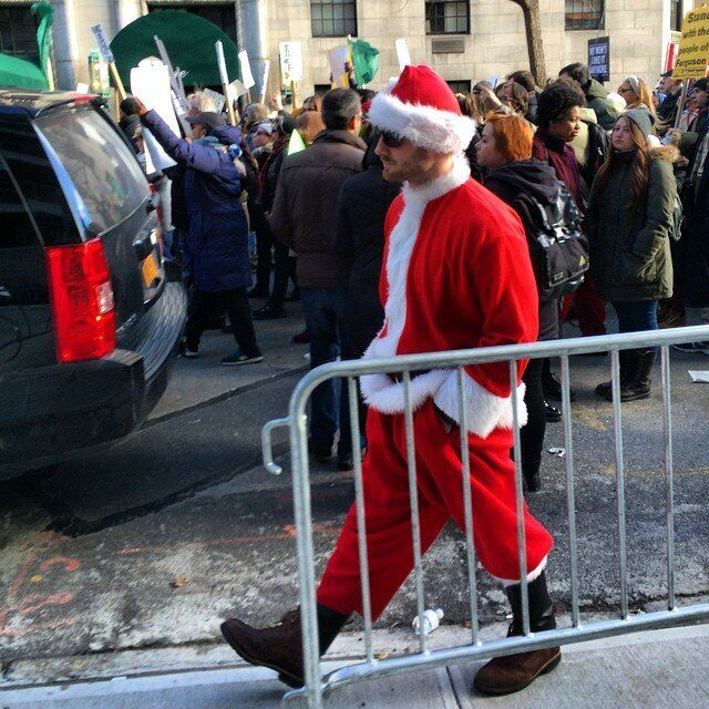 A man dressed up as Santa for SantaCon walk by protesters on 5th Ave. on Dec. 13, 2014 in New York City.