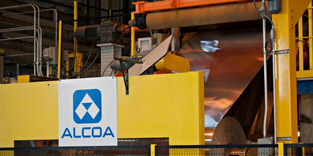 Rolled aluminum is fed into a machine on the auto treatment line at the Alcoa Inc. Davenport Works aluminum facility in River