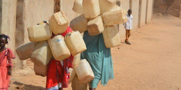 DARFUR, SUDAN - SEPTEMBER 26: Refugee woman carries plastic bottles to get water from a water-well as they try to live under
