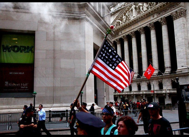 A flag replacing stars with corporate logos passes before the New York Stock Exchange.  Photo © Jaime Rojo