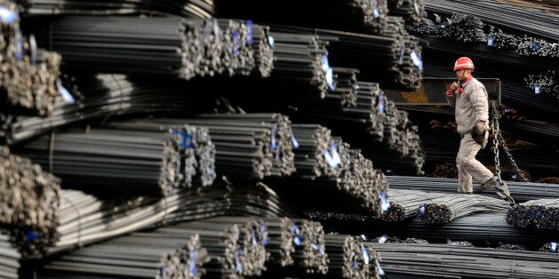 A labourer walks on the steel bars at a steel and iron factory in Changzhi, Shanxi province January 11, 2010. China's imports