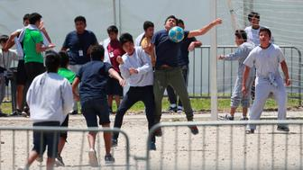 FILE - In this April 19, 2019 file photo, migrant children play soccer at the Homestead Temporary Shelter for Unaccompanied Children on Good Friday in Homestead, Fla. The government has stopped reimbursing some contracted shelters for the cost of teaching immigrant children English-language courses and providing legal services and recreational activities. The Health and Human Services department notified shelters around the country recently that it was not going to reimburse them for teachers' pay or other costs. (AP Photo/Wilfredo Lee, File)