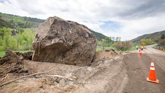 An 8.5 million pound boulder rests next to Colorado State Highway 145 after falling on Friday from nearly 1,000 feet from the nearby ridge and destroying the pavement Monday, May 27, 2019 between Cortez and Tulleride, Colo. Colorado Department of Transportation was able to blast and clean up the other 2.3 million pound boulder on Sunday that fell on the highway after the rockslide that occurred on Friday afternoon. (Hugh Carey/Summit Daily News via AP)