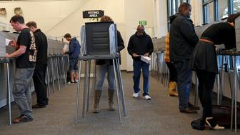 FILE - In this Nov. 4, 2014 file photo, voters fill out their ballots at the Multnomah County Elections Office in Portland, Ore. Oregon Gov. Kate Brown is touting a new report that found nearly 78,000 Oregonians who are 16 and 17 were pre-registered to vote under the state's automatic voter registration law. The law, which is seen as a national model for voter participation, automatically signs Oregonians up to vote when they get a driver's license. (AP Photo/Gosia Wozniacka, File)